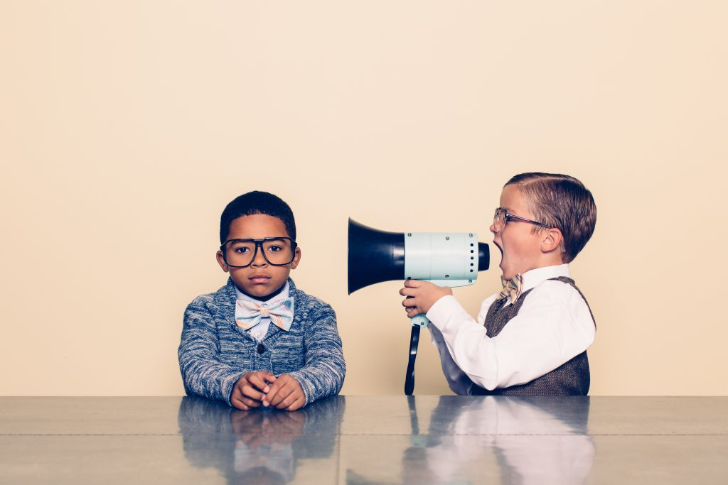 A young boy nerd shouts at the top of his voice to his co-worker through a megaphone trying to talk some sense into him but he is not listening and is ignoring him. The young nerds are dressed in bowties and glasses. Retro styling.